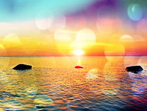 Film effect. Romantic morning at sea. Big boulders sticking out from smooth wavy sea. Pink horizon with first hot sun rays. Film grain effect. Romantic morning stock image