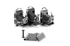 film 120 för retro kameror för medelformat på vit bakgrund med skuggor, tre oskarpa tappningkameror på bakgrund, svart och w Arkivbild