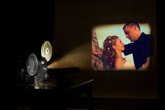 Film festival. Film projector projecting a movie. Love couple on a screen. Film festival concept Royalty Free Stock Images