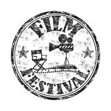 Film festival rubber stamp. Black grunge rubber stamp with movie projector, director chair, filmstrip and the text film festival written inside the stamp Royalty Free Stock Photo
