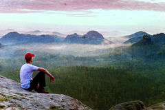 Film grain. Adult sportsman in white shirt, dark trousars and red cap. Man sit on sharp cliff. Film grain effect. Adult sportsman in white shirt, dark trousars Stock Photo