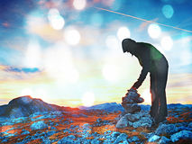 Film grain effect. Alone adult man is stocking stone to pyramid. Alps mountain summit,. Evening sun at horizon. Mountains increased from humidity Film scratch royalty free stock image