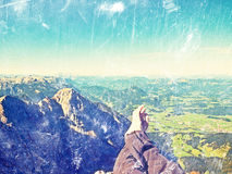 Film grain effect.  The crossed legs take a  rest on tiring mountain trail. Sweaty male legs relaxing on peak of mountain Royalty Free Stock Image