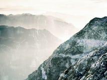 Film grain effect.  Fantastic dreamy sunrise, sharp contour of mountain above mist. Royalty Free Stock Image