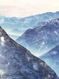 Film grain effect.  Fantastic dreamy sunrise, sharp contour of mountain above mist. Royalty Free Stock Photography