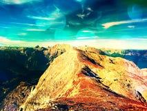Film grain effect.  Fantastic dreamy sunrise, sharp contour of mountain above mist. Stock Photos
