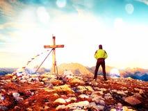 Film grain effect.  Man walk along the cross at mountain peak built to Alps victiims. Royalty Free Stock Photo
