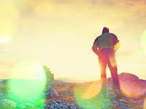 Film grain effect.   Tourist guide at stocked stones on Alps peak. Strong hiker enjoy sunset Royalty Free Stock Images