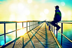 Film grain. Man in warm jacket and baseball cap sit on pier handrail construction and enjoy morning at sea. Sunny clear blue sky,. Film grain effect. Man in warm Royalty Free Stock Photography