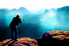 Film grain. Professional on cliff. Nature photographer takes photos with mirror camera on mountaiin peak. Film grain effect.  Professional on cliff. Nature Royalty Free Stock Photography