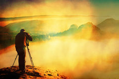 Film grain. Professional on cliff. Nature photographer takes photos with mirror camera on peak of rock. Dreamy fogy landscape. Film grain effect.  Professional Stock Image
