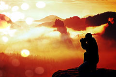 Film grain. Professional photographer silhouette above a clouds sea, misty mountains Stock Photos