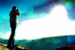 Film grain. Professional photographer takes photos with big camera on peak of rock. Dreamy misty landscape, hot Sun above Royalty Free Stock Photos