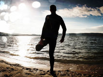 Film grain. Silhouette of person in sportswear and short hair on beach seeing into morning Sun above sea. Film grain effect. Silhouette of person in sportswear Royalty Free Stock Images