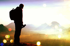 Film grain. Silhouette of photographer overlooking a blanket of fog over valley to sun. Film grain effect. Silhouette of photographer overlooking a blanket of Stock Image