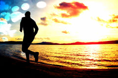 Film grain. Silhouette of sport active man running and exercising on the beach at sunset. Film grain effect. Silhouette of sport active man running and Stock Images
