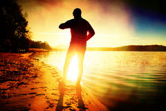 Film grain. Sportsman  running at amazing summer sunset along coastline in sport and healthy lifestyle concept Royalty Free Stock Photo