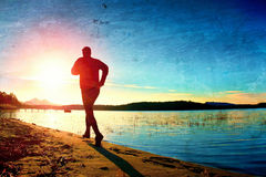 Film grain. Sportsman running at amazing summer sunset along coastline in sport and healthy possitive lifestyle concept Royalty Free Stock Photography