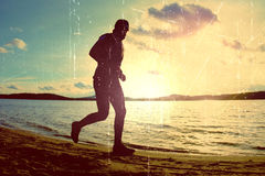 Film grain. Tall man with sunglass and dark cap is  running on the beach at sunset Royalty Free Stock Photos