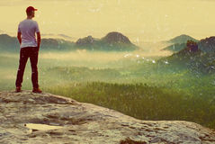 Film grain. Tall man in white shirt and  black trousers with red baseball cap  stay on sharp cliff and watch to valley. Colorful Stock Photo