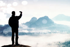 Film grain. Tall tourist is taking selfie on peak above valley.  Smart phone photography Stock Images