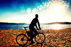 Film grain. Young man cyclist sit on bike,  blue sky and sunset background on beach. End of season at lake and popular tourist res. Film grain effect. Young man Royalty Free Stock Images