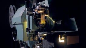 Film hat im Filmprojektor beendet Alter Filmprojektor, der in der Dunkelheit arbeitet Transportwagenschuß Abschluss oben stock video footage