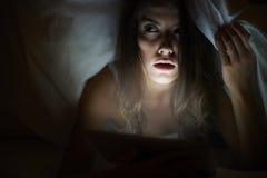 Film horror di sorveglianza della donna sulla compressa fotografia stock