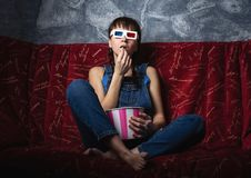 Film industry: A girl in 3D colored glasses watching a movie at home on a red sofa and eating popcorn from a striped box stock images