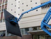Film Lighting Technician at work. Royalty Free Stock Photo