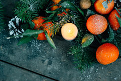 Film look image Christmas composition with Tangerines, Pine cones, Walnuts and Candles on Wooden Background, holiday decoration Royalty Free Stock Photography