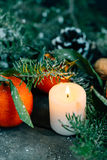 Film look image Christmas composition with Tangerines, Pine cones, Walnuts and Candles on Wooden Background, holiday decoration Stock Image