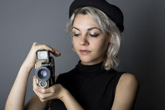 Film Maker or Cinematographer. Woman holding a vintage video camera posing as a director, filmmaker, or cinematographer in the hollywood movie industry.  The Royalty Free Stock Photos