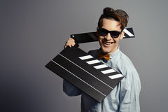 Film man. Cheerful young man holding clapper board. Cinema industry. Different occupations stock photos