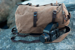 The film medium format camera lies on the stones against the backdrop of a canvas vintage backpack Royalty Free Stock Images