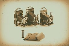 120 film for medium format retro cameras on white background with shadows, blurry vintage cameras on background, antique effect. And vignetting Stock Photography
