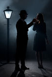 Film noir couple lamppost fog lighting cigarette royalty free stock photos
