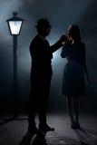 Film noir couple lamppost fog lighting cigarette Royalty Free Stock Photos