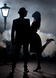Film noir couple lamppost fog. Man and women in cinema noir style expressing love in cinema noir style. They are standing in the mist or fog with a lantern pole Stock Photos