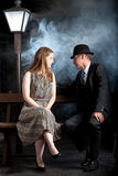 Film noir couple street lantern bench fog mist stock photo