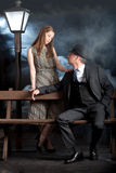 Film noir couple street lantern bench fog mist stock photos