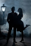 Film noir couple street light mist. Man and girl in cinema noir style expressing love in cinema noir style. They are standing in the mist or fog with a lantern Stock Photography