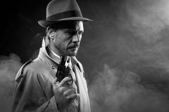 Film noir: detective in the dark with a gun. Handsome detective in trench coat holding a gun in the dark, film noir royalty free stock photography