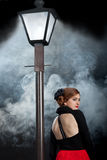 Film noir girl street lamppost fog back stock photography
