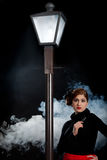 Film noir girl street lantern fog gun royalty free stock images