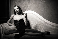 Film noir style: dangerous elegant young woman lying on sofa and smoking cigarette. Black and white Stock Photography