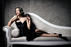 Film noir style: gorgeous beautiful young woman lying on sofa and smoking cigarette Stock Image