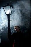 Film noir woman lamppost fog girl Royalty Free Stock Images