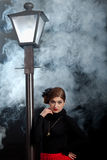 Film noir woman street lamppost mist stock photo