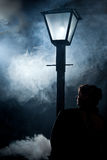 Film noir woman street lantern mist royalty free stock photography